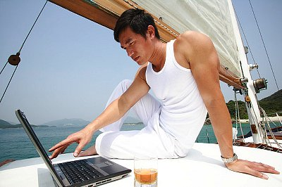 Man Using Laptop on Boat